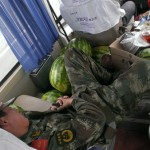 Chinese soldier getting a ride in our bus. The melons around him are some kind of a bribe.