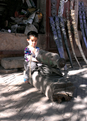 This perhaps 3 year-old boy is already learning from his father, a blacksmith.